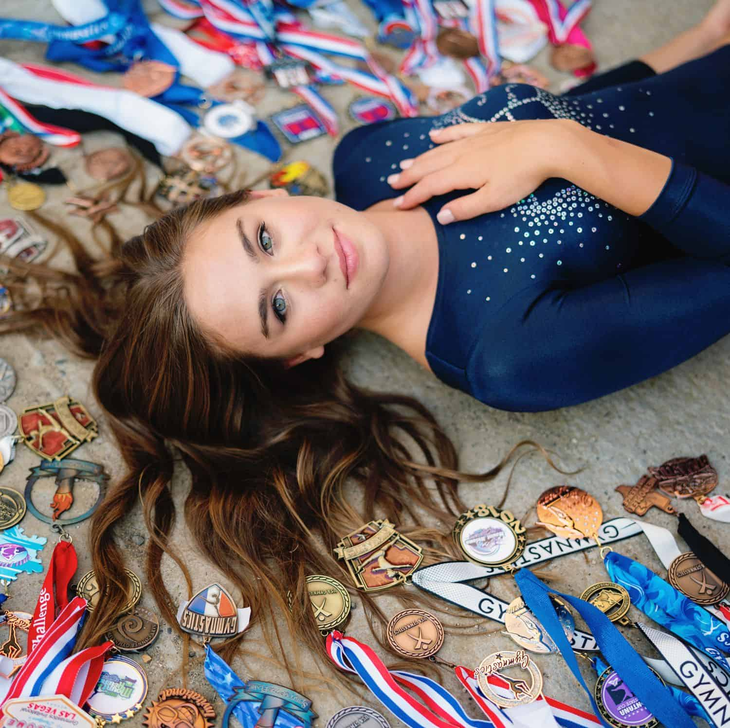 A senior girls lies on the ground surrounded by her medals and awards