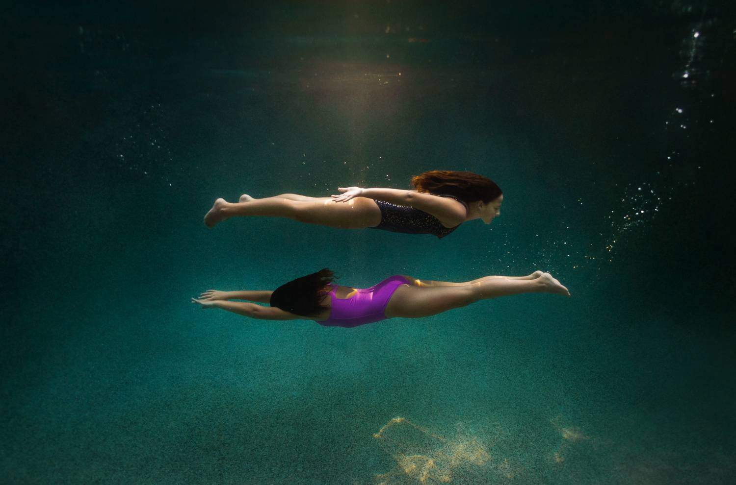 Two children swim underwater. One child is above the other, creating two parallel lines beneath the water