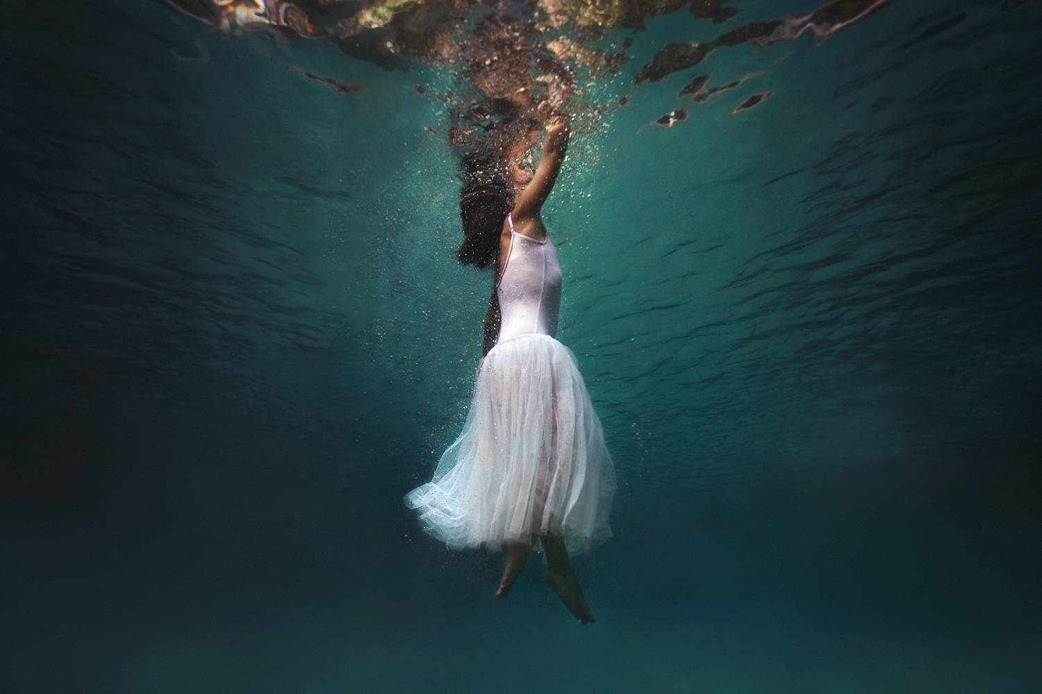 A person in a flowing white dress floats in a blue pool with only their face braking the surface of the water
