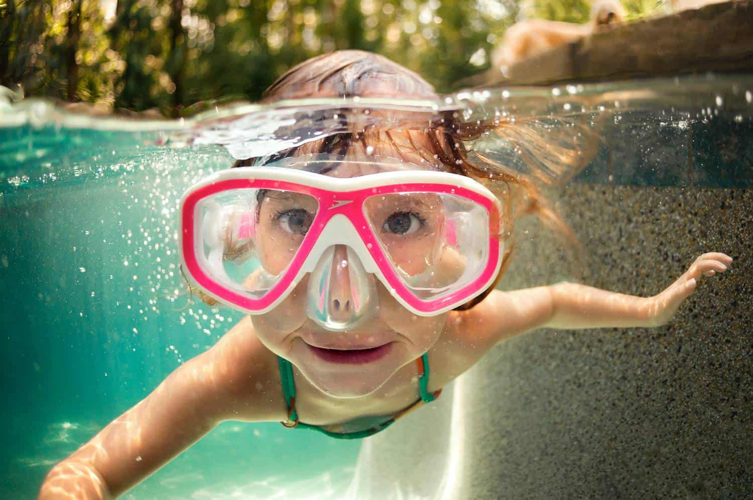 A child in oversized pink goggles swims underwater toward the camera