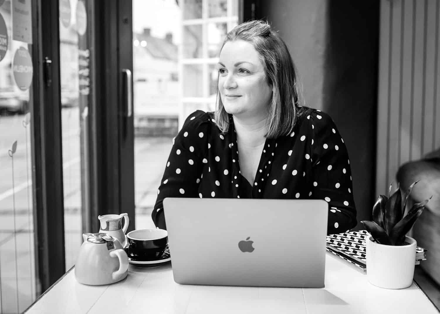 A blonde woman in a black polka-dot dress sits at her laptop in a coffee shop drinking tea