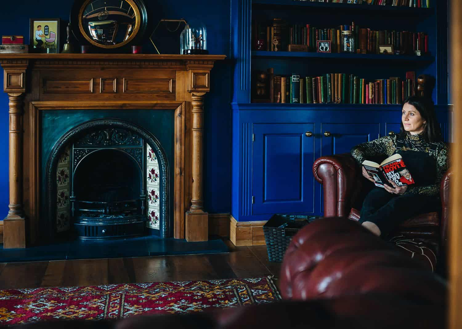 An author sits in a deep leather chair in her blue-painted library reading a book