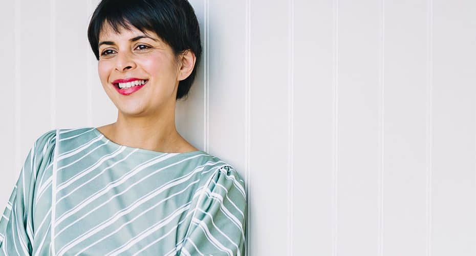 A brunette woman with pink lipstick and a pixie haircut wearing a blue silk dress leans against a white wall smiling