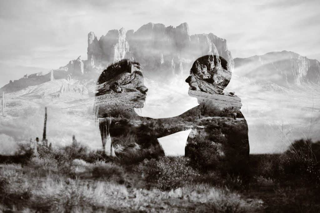 A double exposure of a couple looking at one another in front of a desert canyon