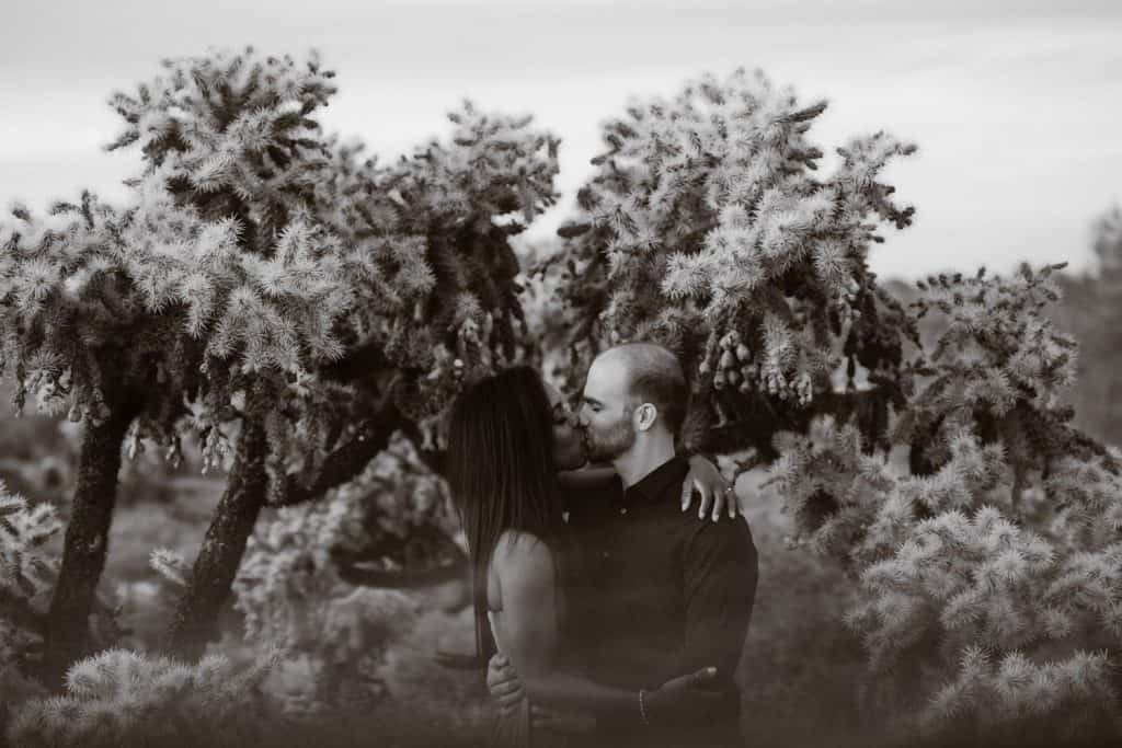 A black and white portrait of an engaged couple kissing in the desert