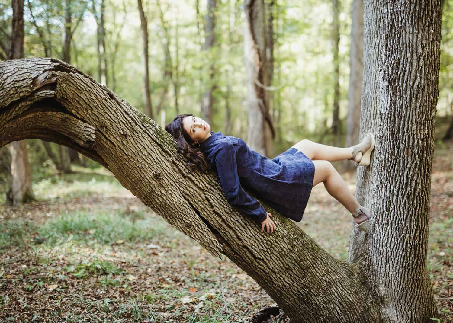 A high school senior girl lies in the fork of a tree wearing a denim dress and no shoes