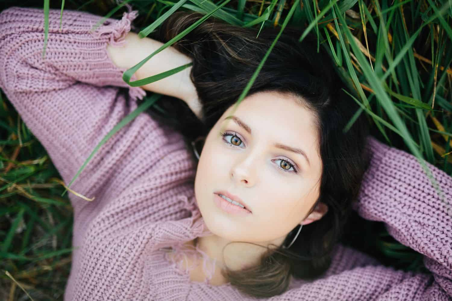 A high school senior in a lavender sweater lies in the green grass with a serious expression on her face