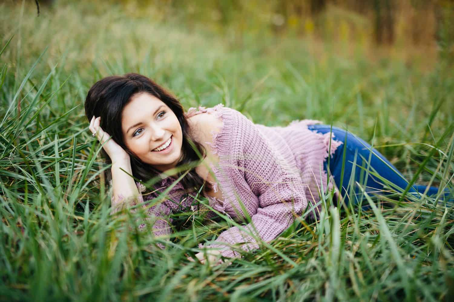 A high school senior wearing a lavender sweater lies on her side in long, green grass