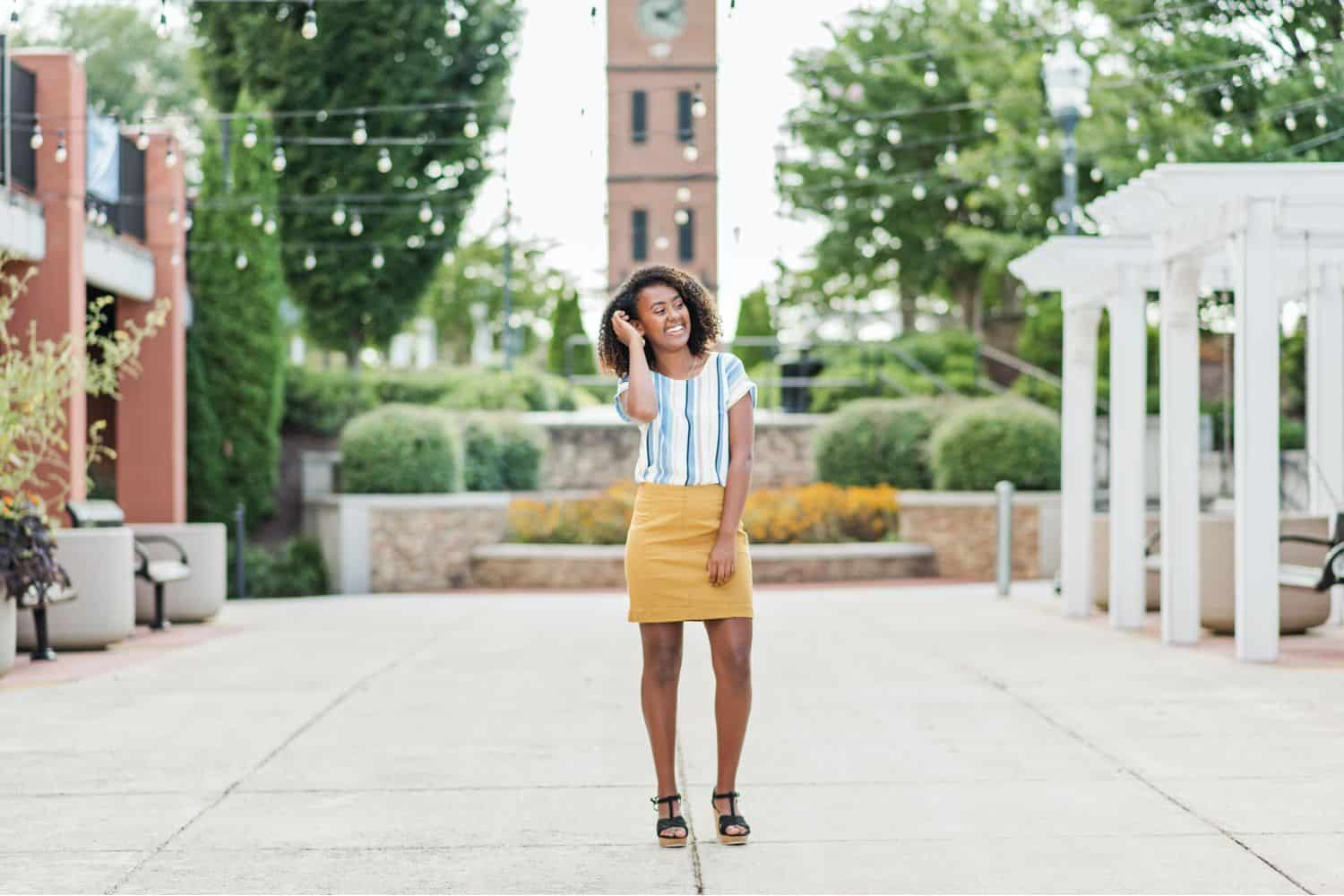 A high school senior girl poses in the town square wearing a mustard yellow mini skirt and a blue-striped white blouse.