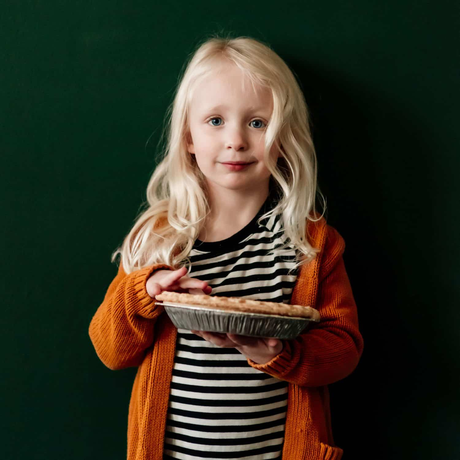 Little girl in an orange sweater smiling while holding a pie