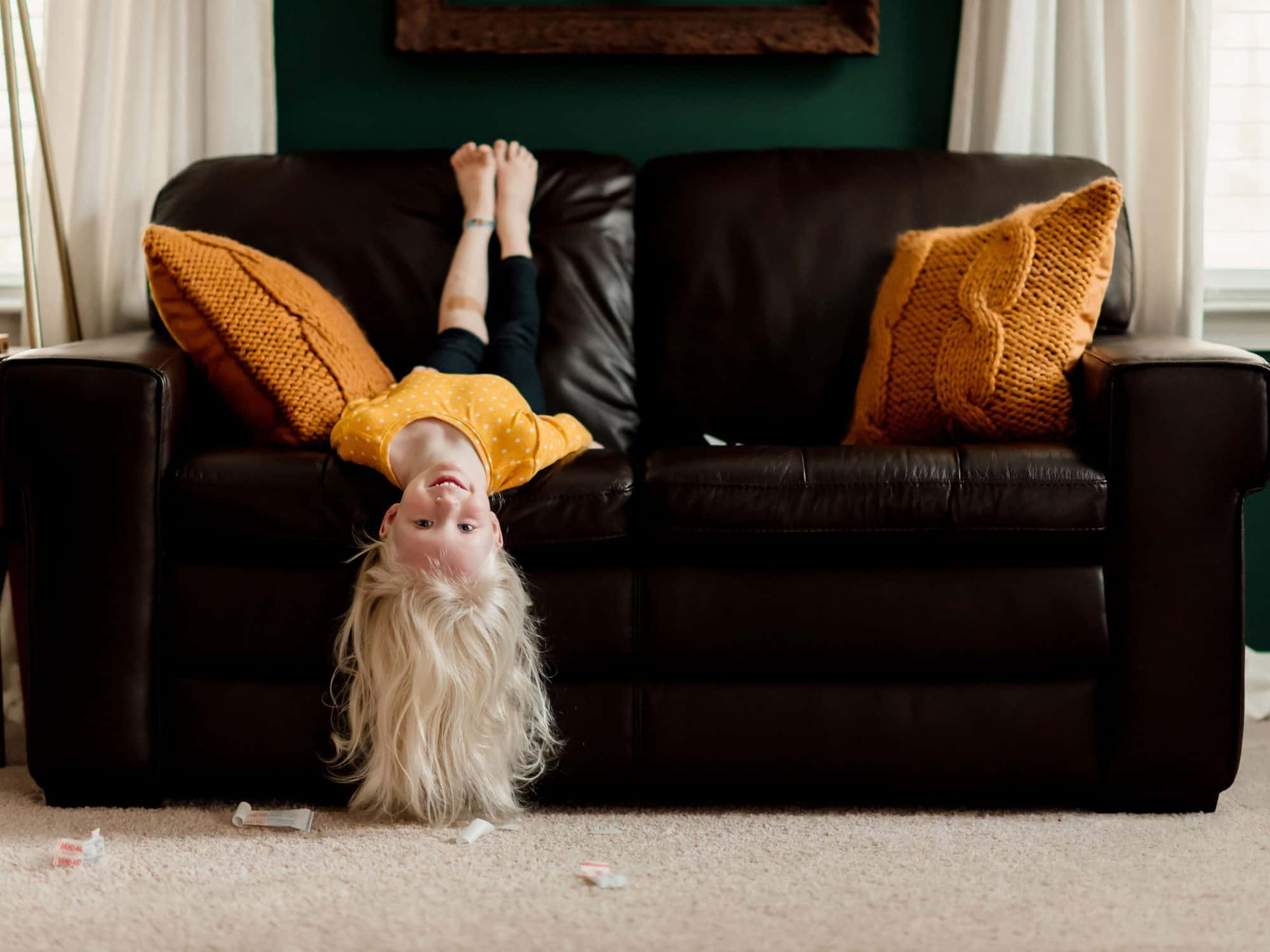 A child hanging off a leather couch upside down