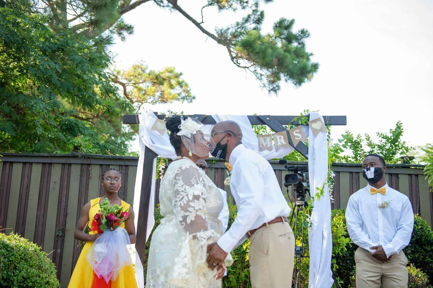 A bride and groom share their first kiss as husband and wife in front of their mask-wearing guests during COVID-19
