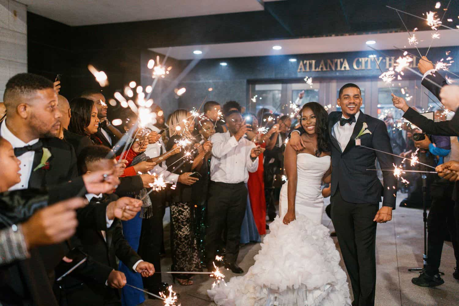 A couple runs through a tunnel of sparklers held by guests at the end of their wedding