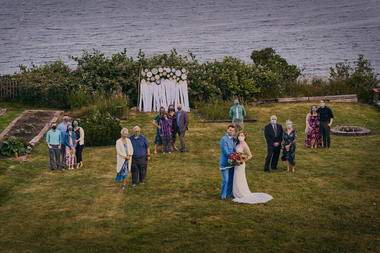 A socially distanced family portrait in a large seaside field after an outdoor wedding during COVID-19