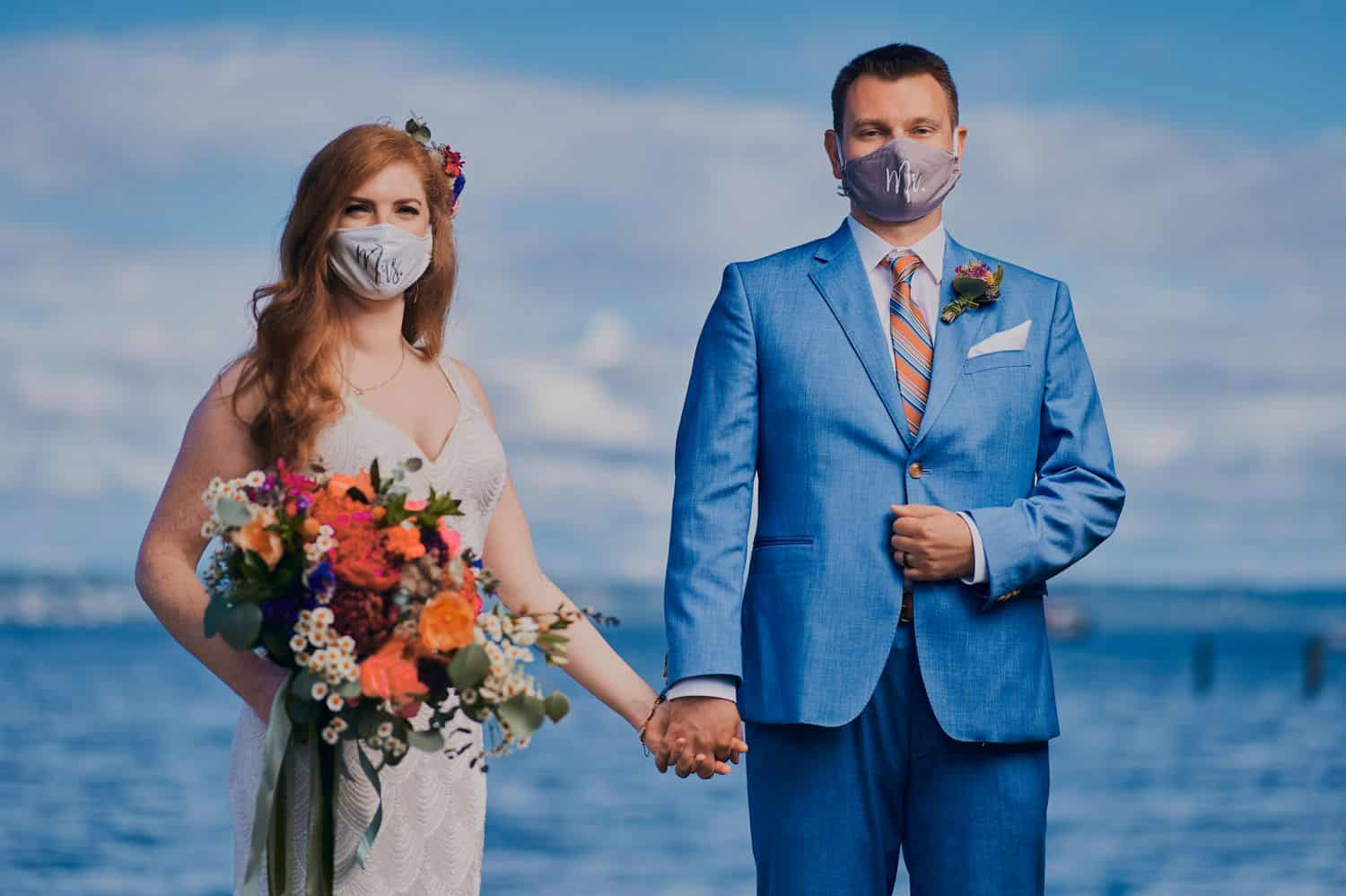 A bride and groom hold hands in front of the ocean with COVID-19 masks on their faces