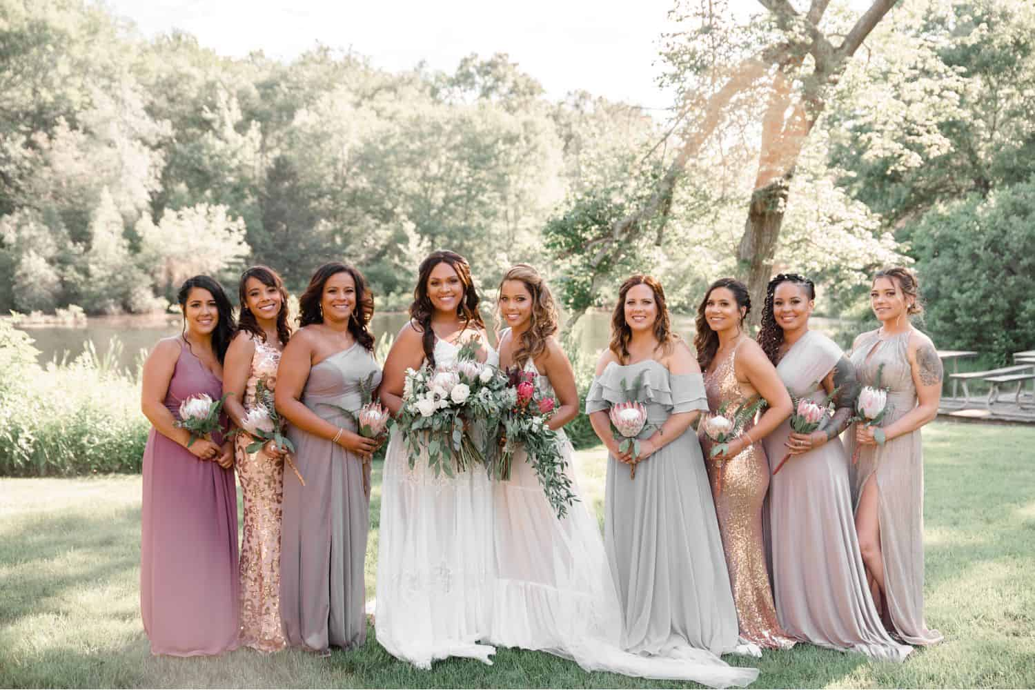 A group photo of two brides and their wedding party