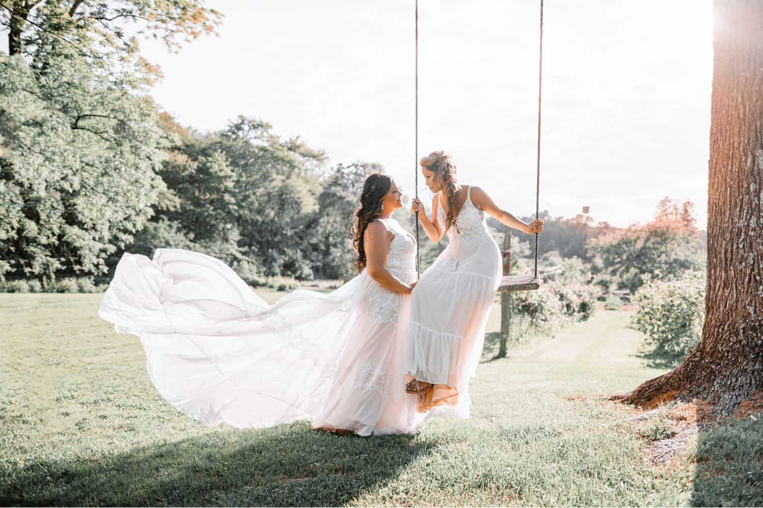 An outdoor wedding portrait of two brides on a swing