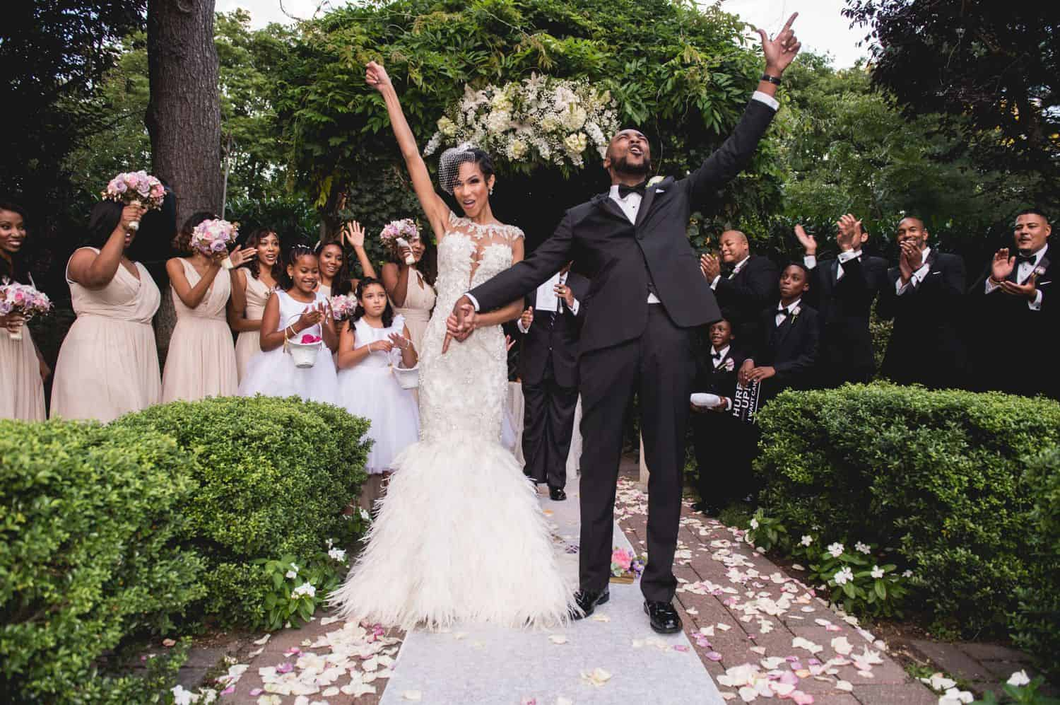 A newlywed couple cheering with their hands up as they walk down the aisle