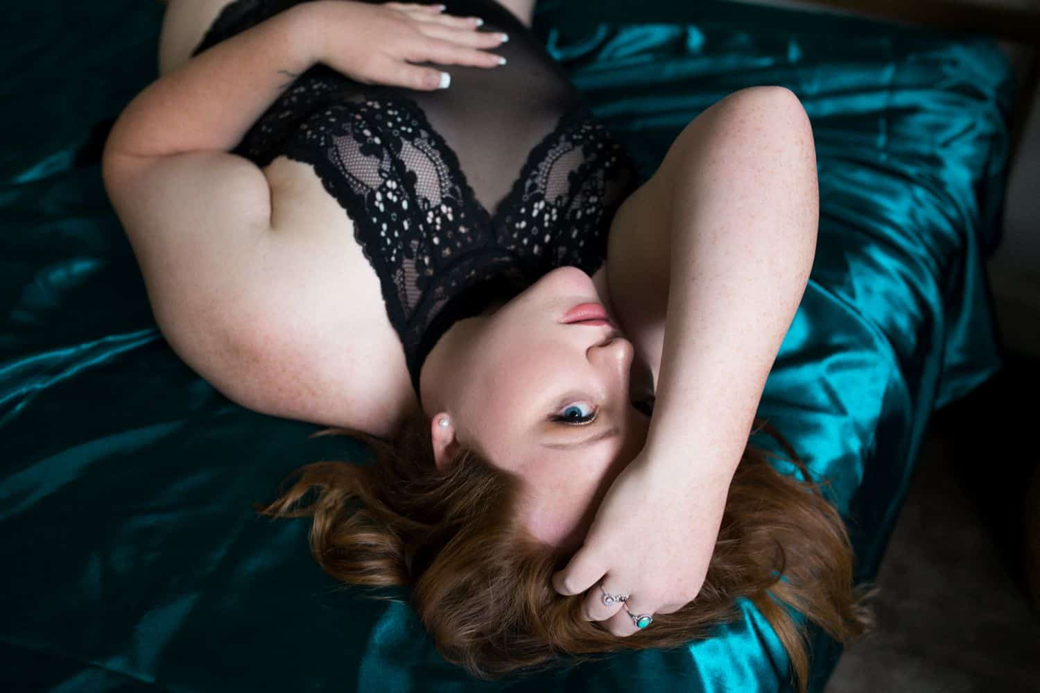 A white individual wearing black lingerie lies on a teal satin bed while being photographed by Kinzie Ferguson, the Empowerment Photographer