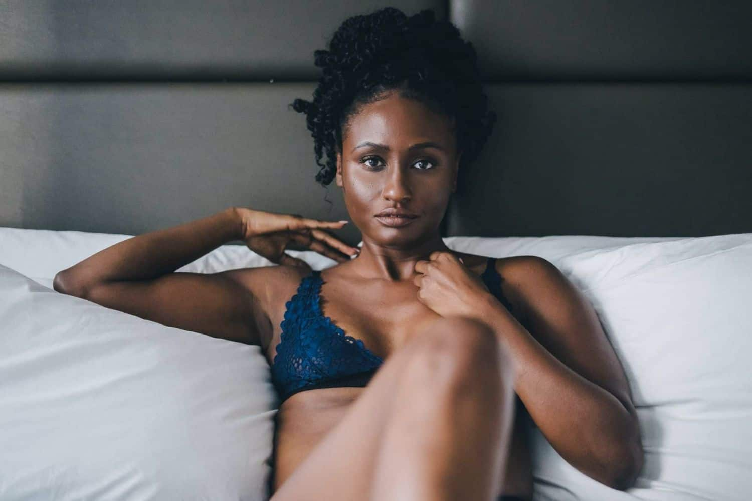 A person with dark skin and blue lingerie reclines on a white bed for a boudoir session by Toni Black.