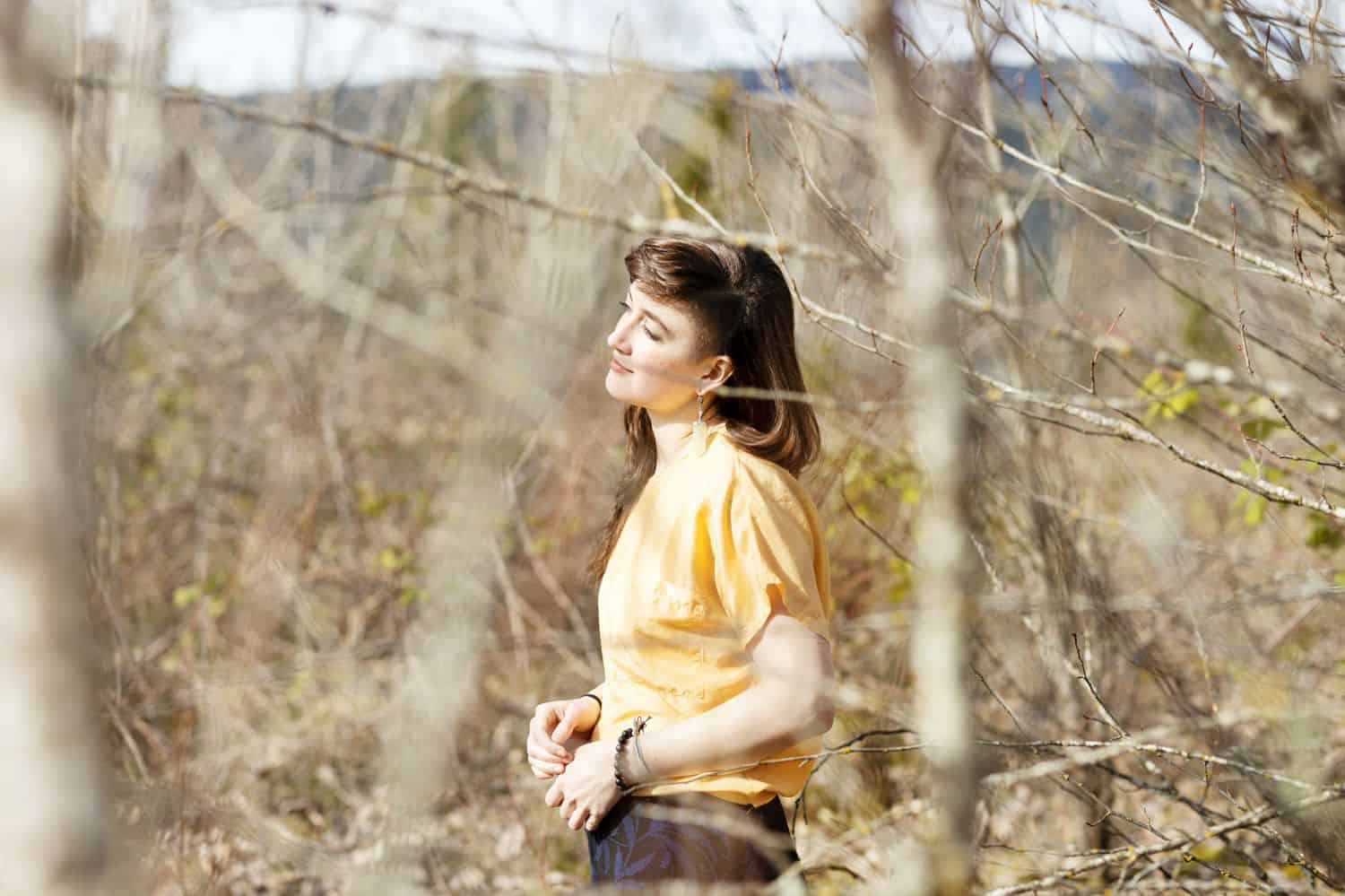 A person in a yellow shirt faces the sun while standing in the woods being photographed by Sofia Angelina