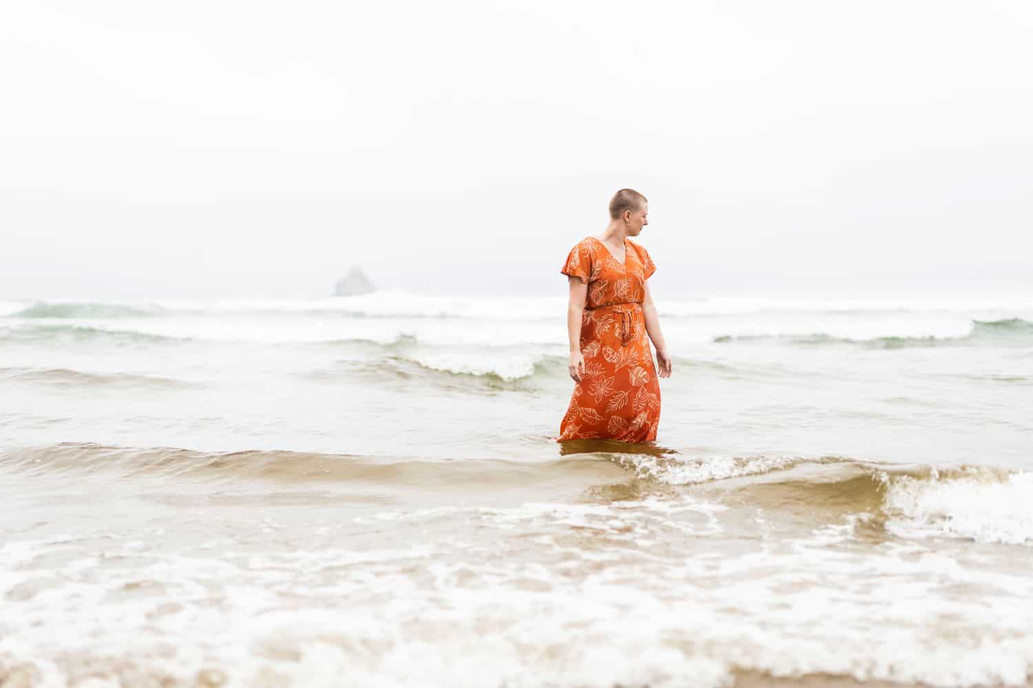 A person with a shaved head wearing a rust-colored dress stands in the ocean waves while photographer Sofia Angelina conducts a healing session that addresses chronic pain.