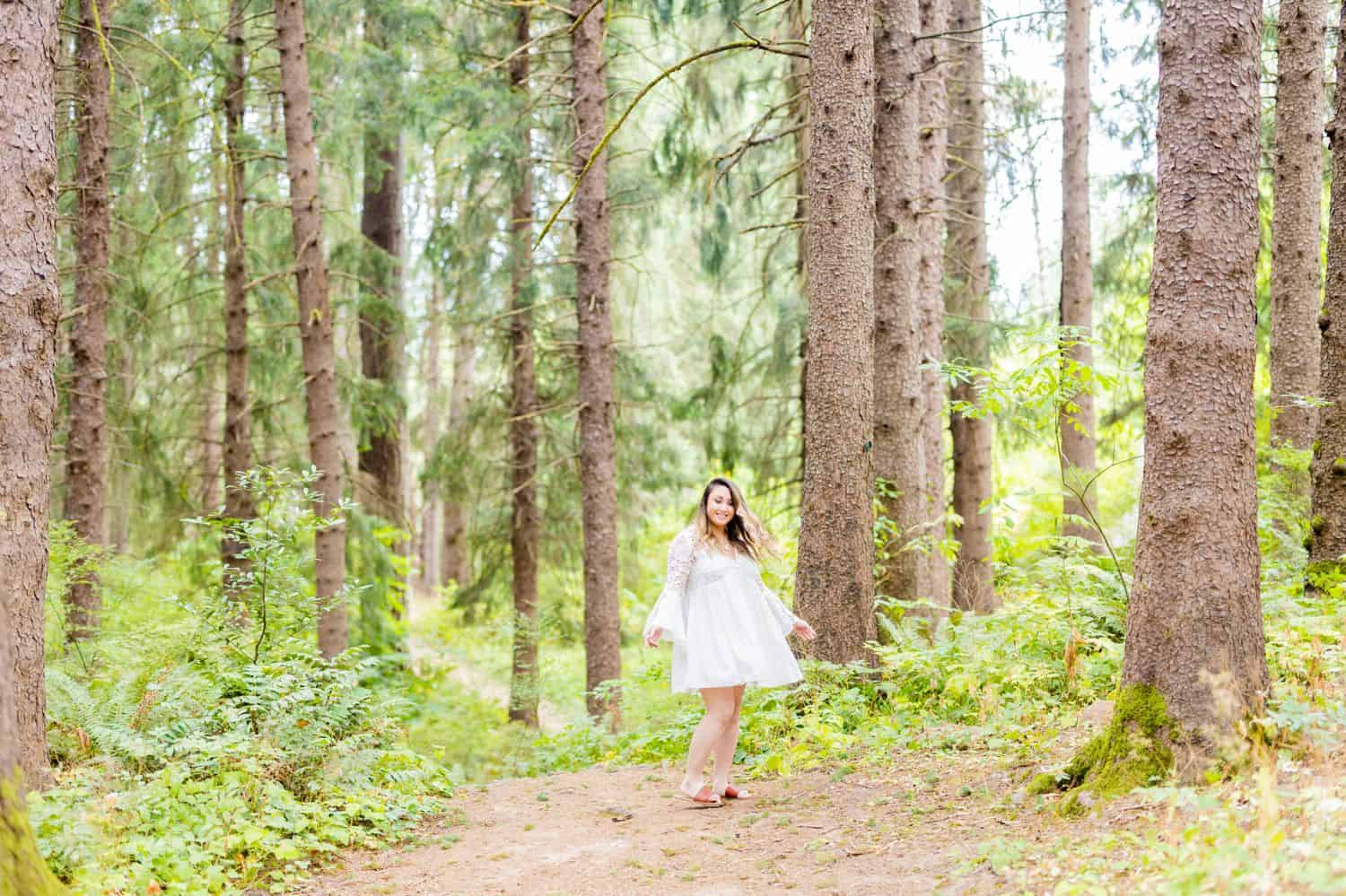 A person in a flowing white dress twirls in the Oregon forest while Sofia Angelina makes photographs