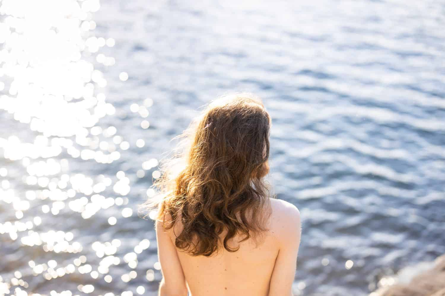 A person wearing no shirt is photographed sitting at the edge of the ocean by Sofia Angelina.