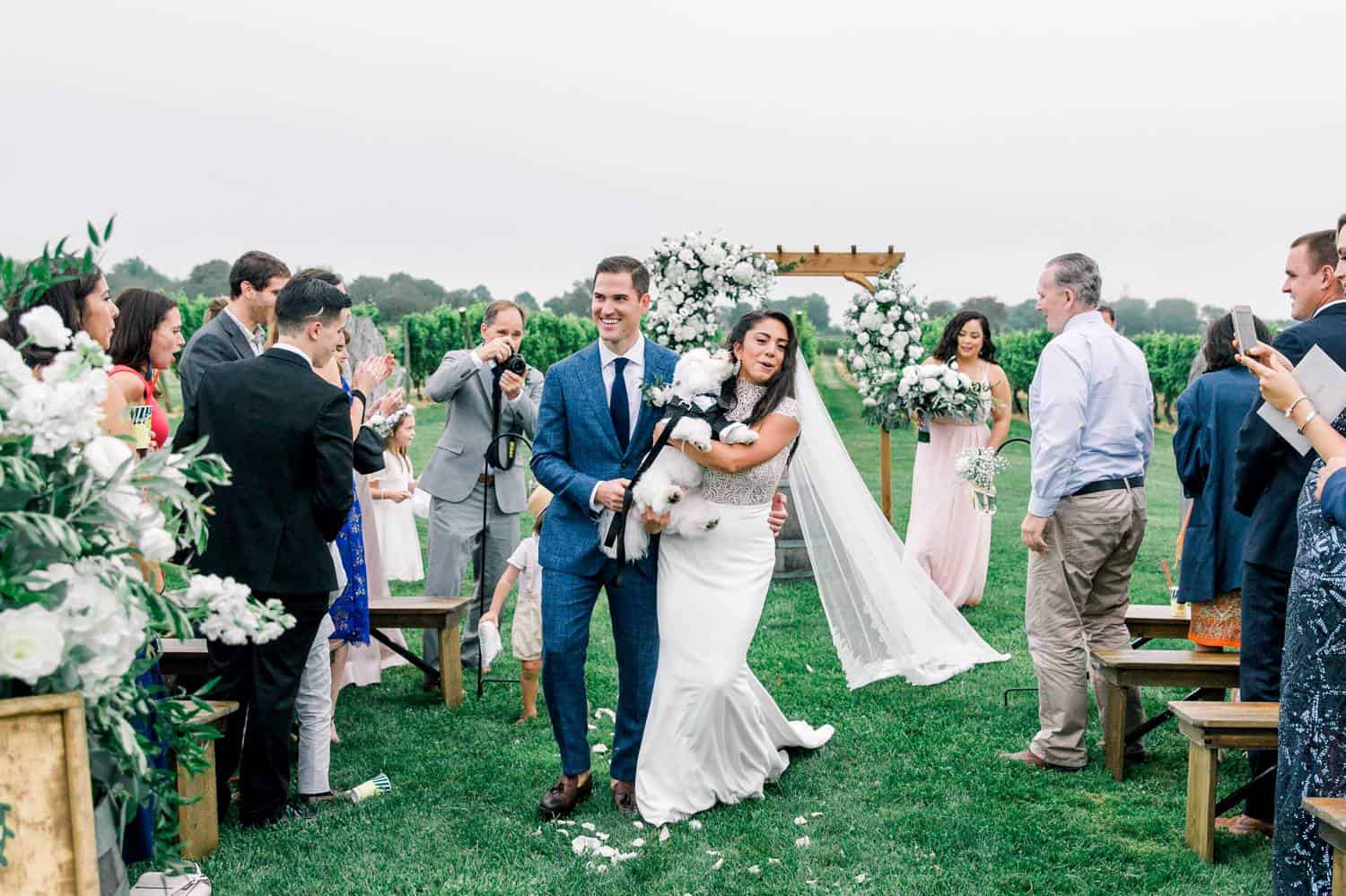 A newly married couple walks down the aisle carrying their fluffy white dog as their guests stand and cheer.