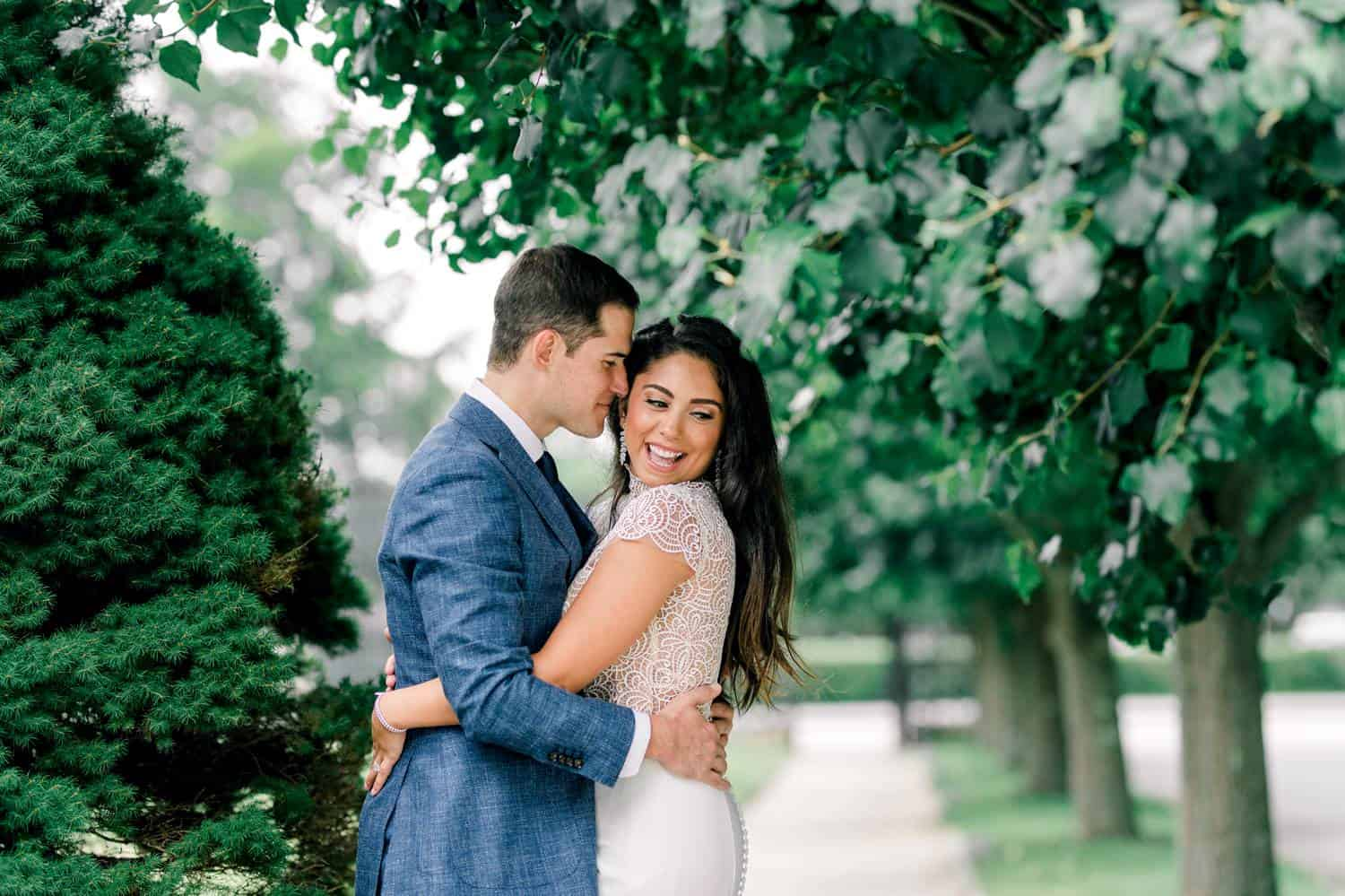 A bride and groom stand outside on a shady sidewalk. The groom embraces the bride with his face pressed against the side of her face.