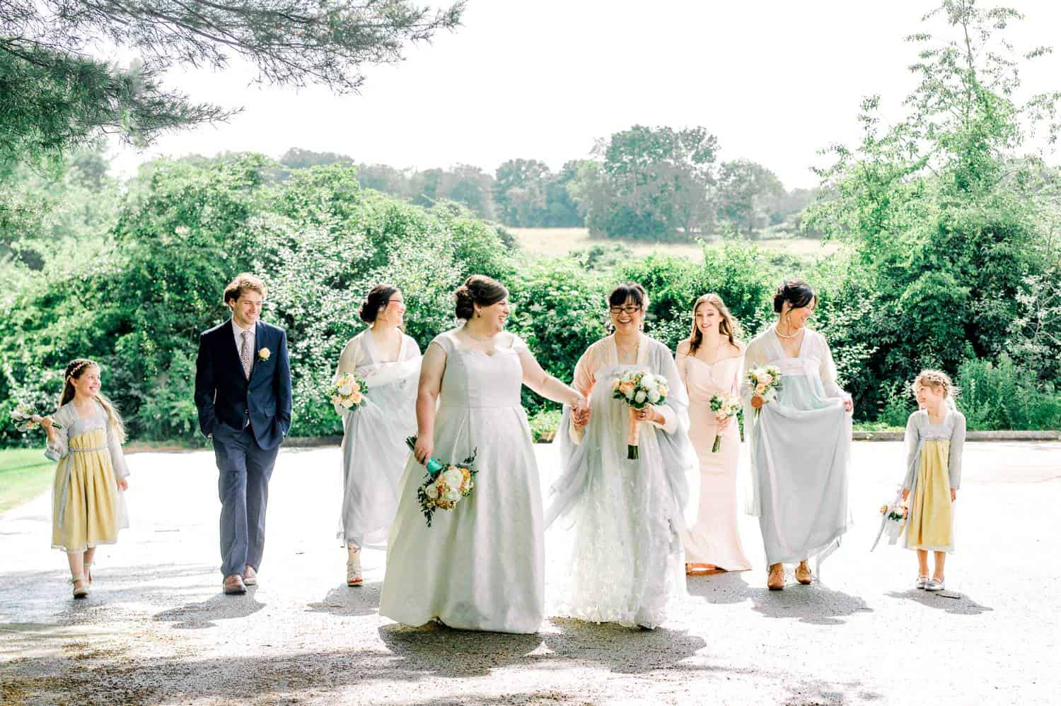 Two brides stroll under a tree. They are backlit by the bright sun, and surrounded by their wedding party.