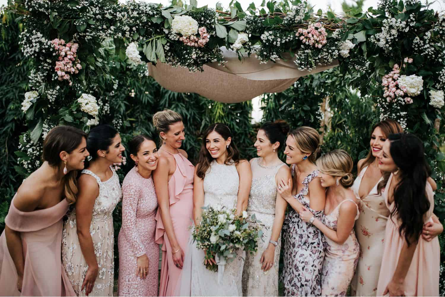 Wedding Print Packages: A bride and her bridesmaids stand under a floral chuppah.