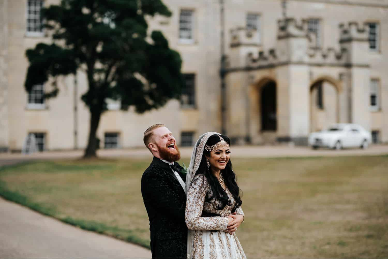 Wedding Print Packages: Bearded groom stands behind bride dressed in traditional Indian wedding attire. A castle is in the background.