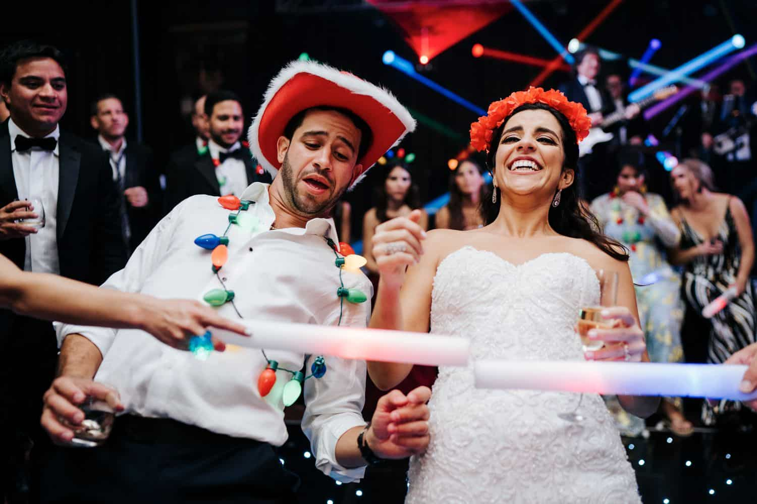 Wedding Print Packages: A bride and groom dance in silly hats at their reception. They are surrounded by guests holding glow sticks.