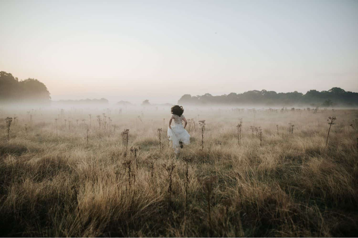 Wedding Print Packages: A bride runs away from the camera through a misty field.