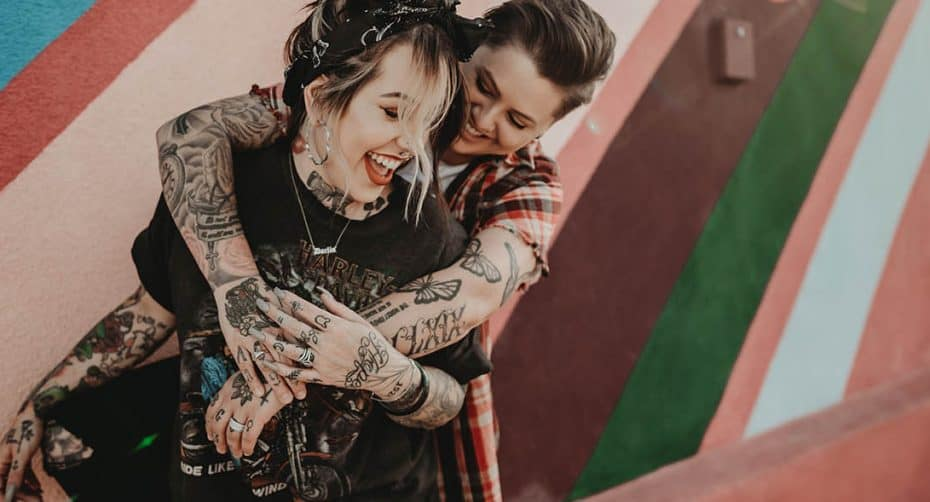 Two people with tons of beautiful tattoos snuggle close with their arms around each other. They are both laughing. The wall behind them is painted like a vintage rainbow.