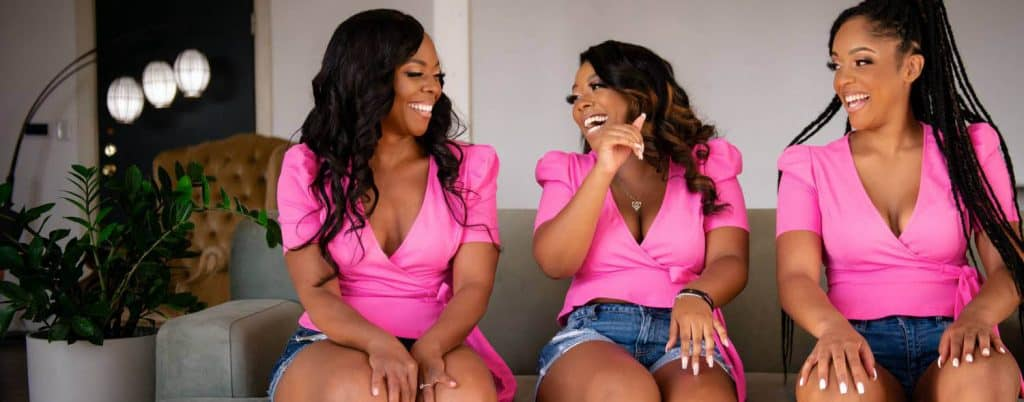 Three Black women sit together on a sofa, laughing. Their hair and makeup are styled, and they all wear the same bright pink wrap shirt with puffed sleeves.