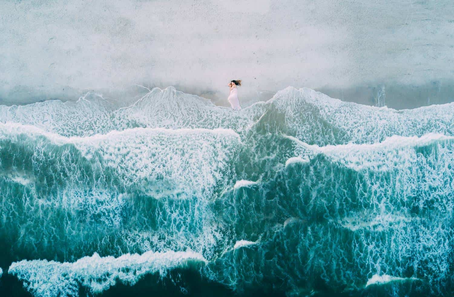 A fine-art drone photograph depicts the tiny image of a white-dressed pregnant woman reclining on a beach above a bright blue ocean's waves.