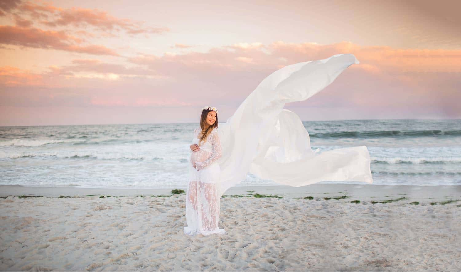 A pregnant woman stands on a beach at sunset. The sand is almost white, and dotted with footprints; and the sky is a beautiful pink tone. The pregnant woman wears a semi-sheer, lace, white gown that's billowing in the wind behind her. She cradles her baby bump as she looks back over her shoulder along the beach.