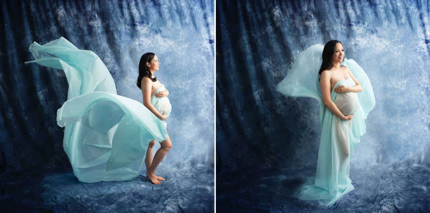 A pregnant woman is photographed against a deep blue studio backdrop. A light teal gown swirls around her.