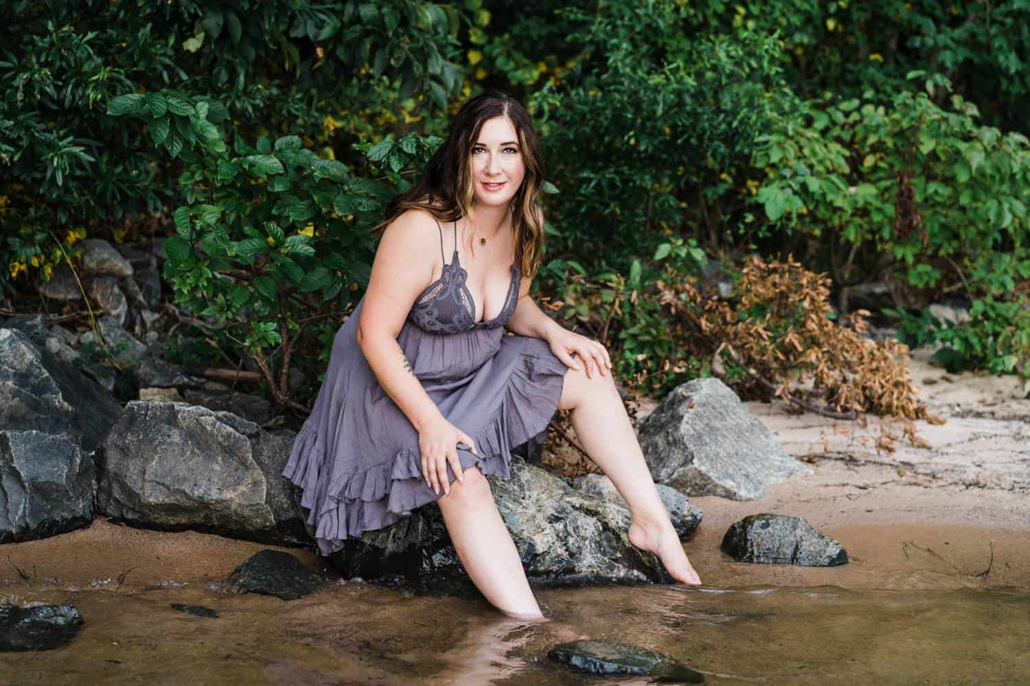 A woman in a short purple nightie sits at the edge of a creek with her feet in the water