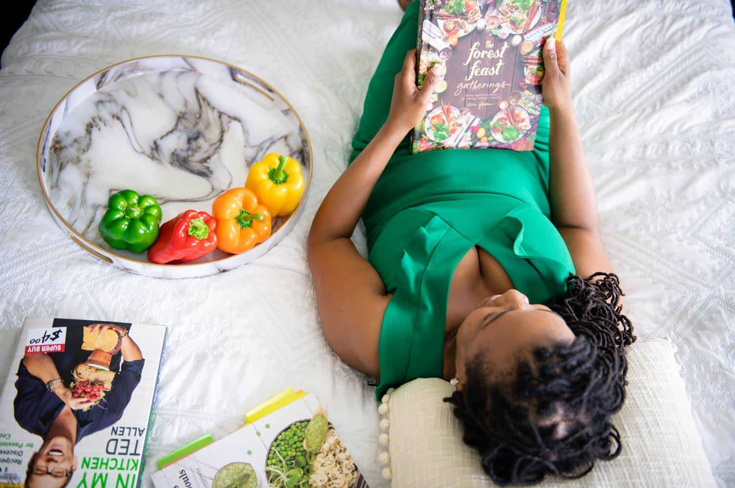 A Black woman in a satin, emerald green dress lies on a white bed reading a food magazine. Beside her is a marble tray of fruits and vegetables, along with a small stack of recipe magazines.