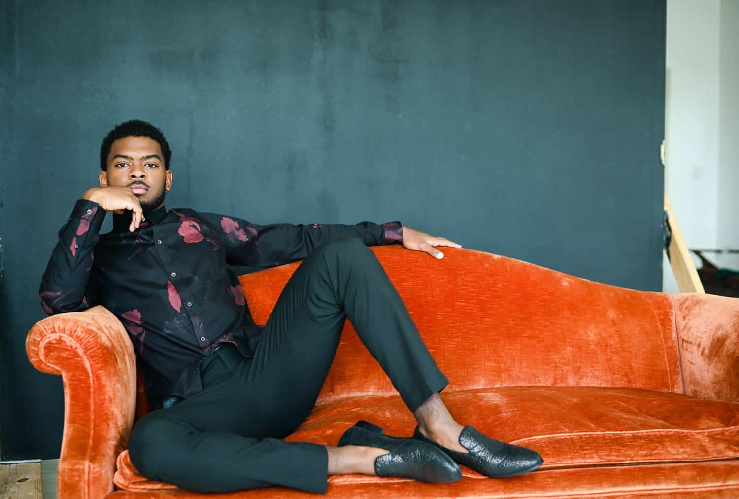 A dapper Black gentleman in black pants, a floral shirt, and alligator shoes sits casually on an orange velvet sofa with his feet propped up beside him. The photo is taken in a studio against a deep gray backdrop, and the man's rests his elbow on the sofa's arm so he can rest his chin in his hand.
