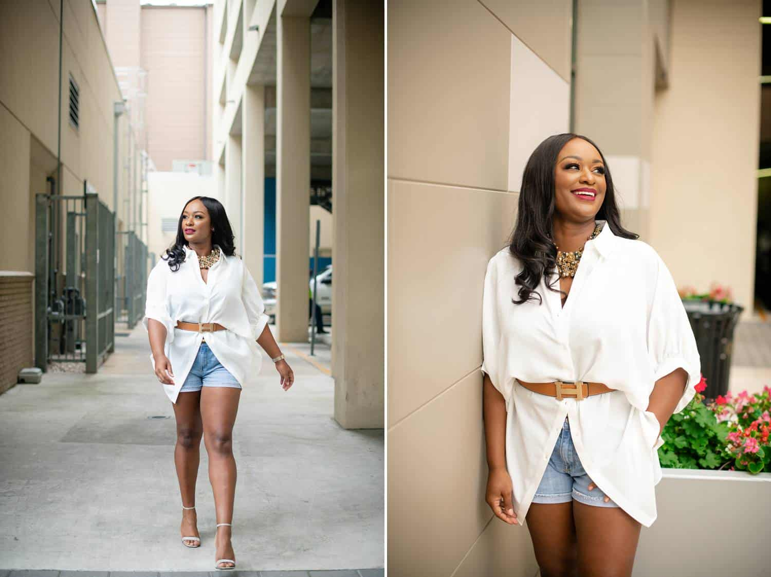 A Black woman in denim shorts and a leather-belted white top strolls through a neutral colored alleyway.