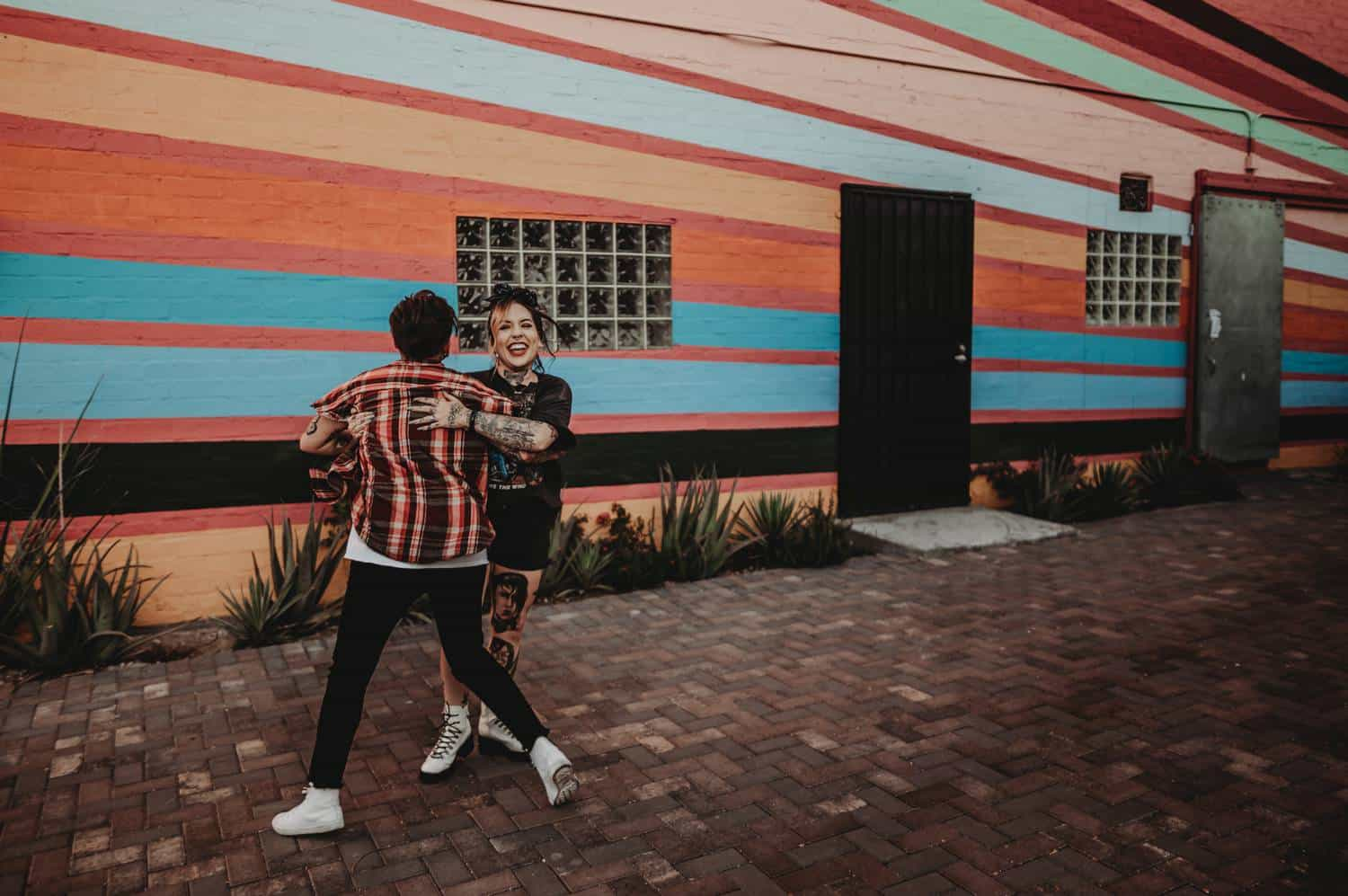 A couple dances joyfully on a stone-paved pathway into a rainbow-striped building.