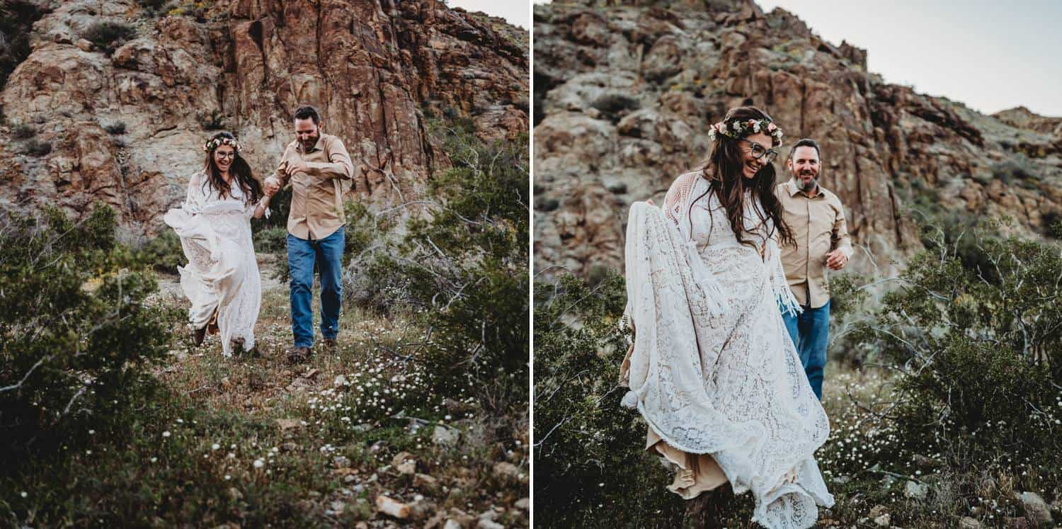 A white-gowned bride holds hands with her more casually dressed groom as they skip together through the grass at the foot of red desert mountains.
