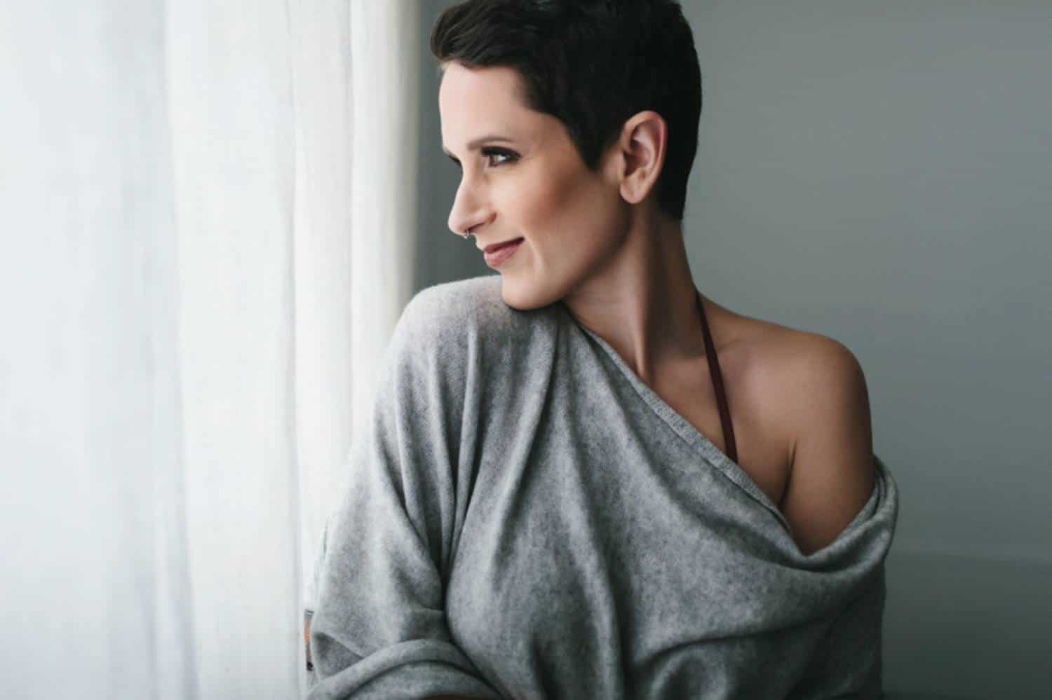 A woman with a brunette pixie cut, wearing a gray cashmere sweater that has slipped off one shoulder, looks over her shoulder out the window with a slight smile on her face. Learn how to take boudoir photos for clothed clients by reading the ShootProof blog!
