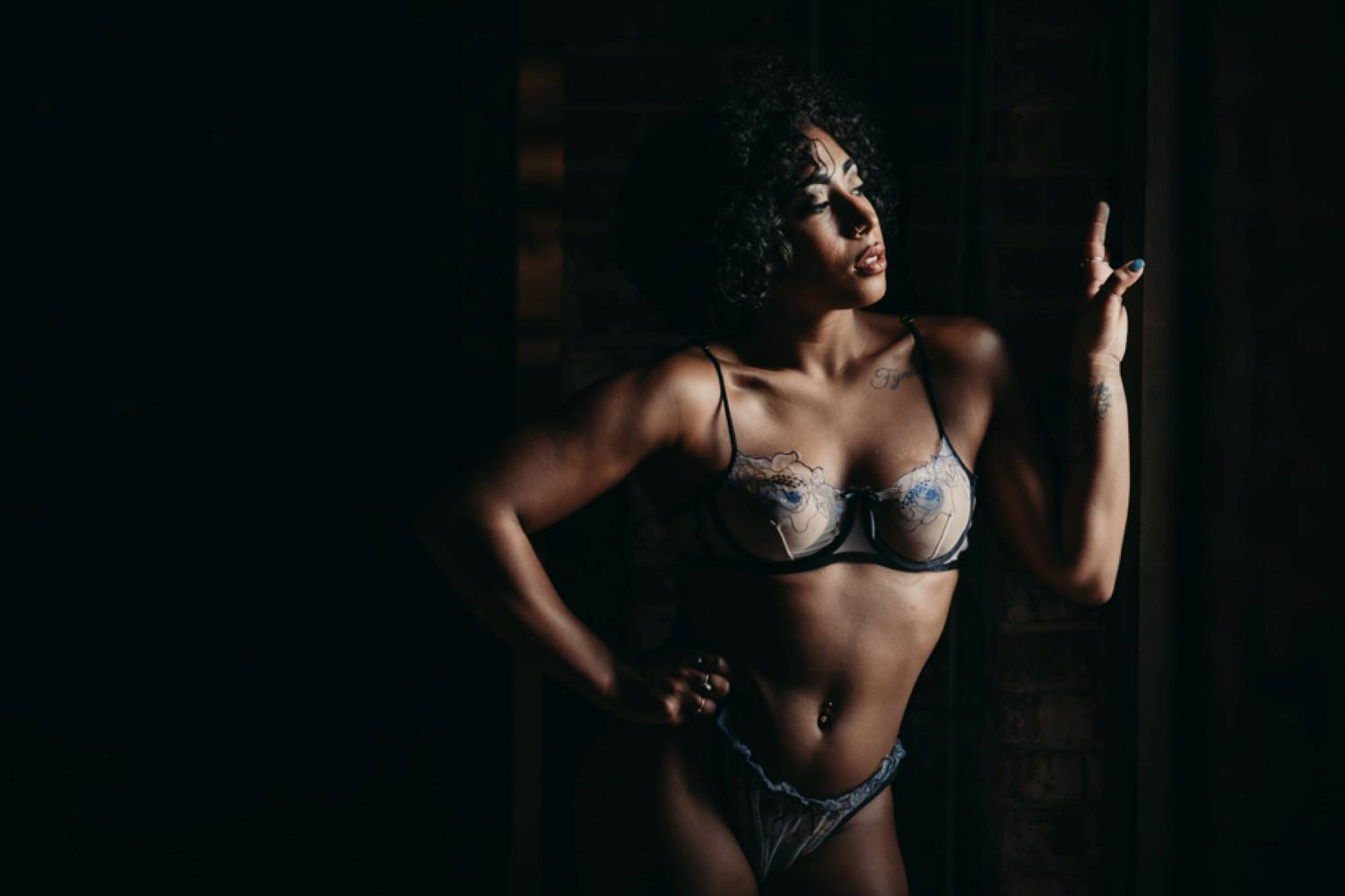 A woman in a purple bra and panties stands in window light and poses so her muscles are well-defined. Learn how to take boudoir photos like this one and more!