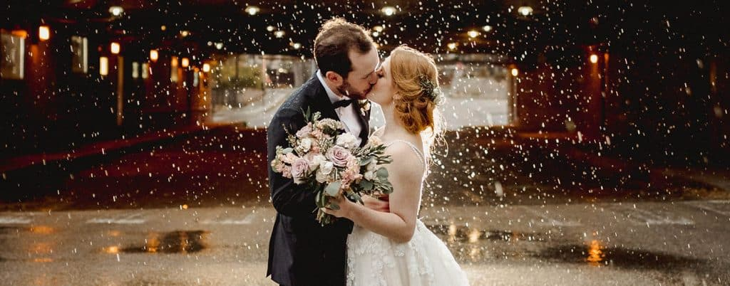 A wedding couple kisses in the rain in front of a train trestle. They're illuminated by an off-camera flash and photographed by Black & Gold Photography.