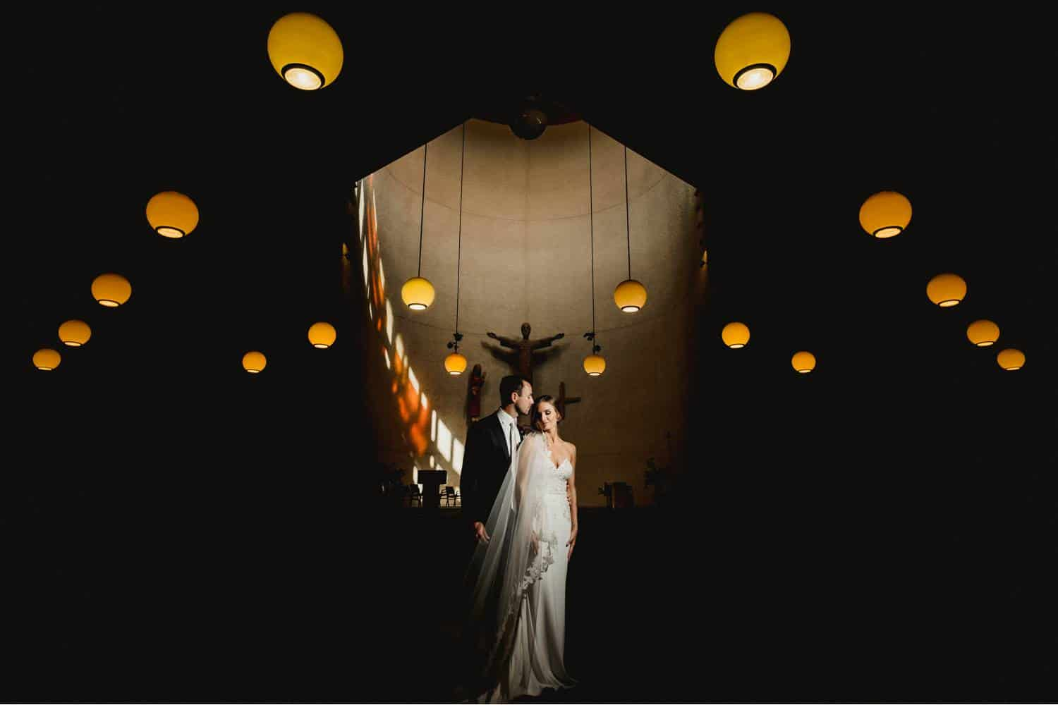A bride wearing a long veil stands calmly beside a groom who looks solemnly at her face. Behind them, the sculpture of a saint is centered on a broad wall surrounded by round, hanging lamps. Black & Gold Photography makes stunning wedding portraits using off-camera flash.